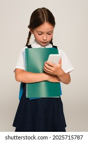 schoolchild holding notebooks while looking at mobile phone isolated on grey