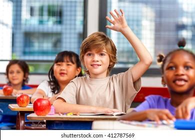 Schoolchild raising hand in classroom. Education concept.