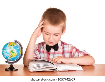 Schoolchild reads the book, next to globe isolated on white