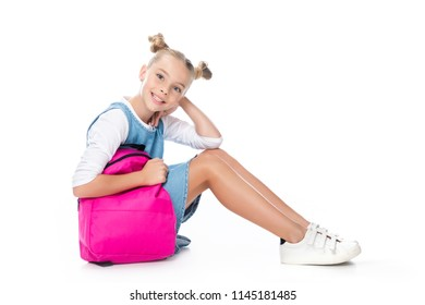 schoolchild sitting with pink backpack and looking at camera isolated on white