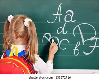 Schoolchild writting on blackboard. Rear view.