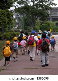 "Schoolchildren group walking in a park together with their educators.Useful image to include it in a ""Back to school"" design"
