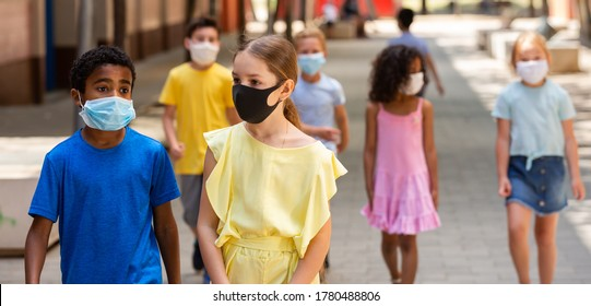 Schoolchildren in masks walking together on the street from school