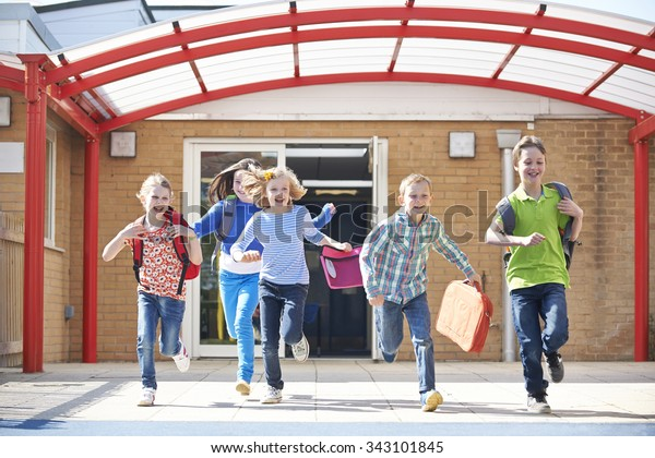 Schoolchildren Running Into Playground At End Of Class