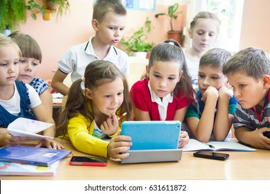 Schoolchildren together study a tablet in school class