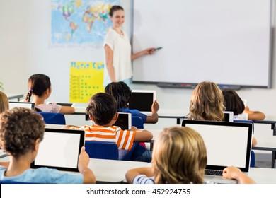 Schoolchildren using digital tablets against female teacher teaching them in classroom