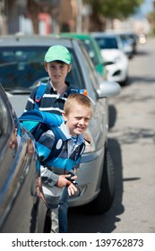 Schoolchildren waiting between the parked car outdoors