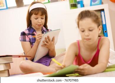 Schoolchildren writing into booklet at home, doing homework.?