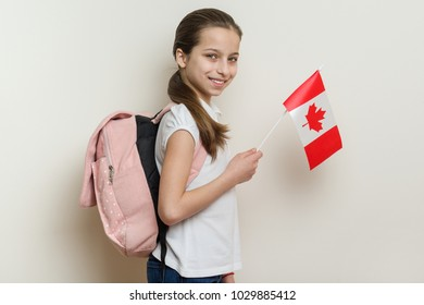 Schoolgirl 10 years in white T-shirt with a backpack holding the flag of Canada, background bright wall in the school.