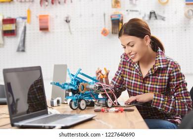schoolgirl adjusts the robot car model, women in a robotics laboratory