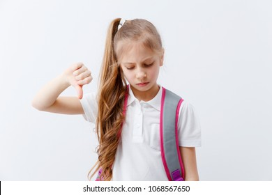 A schoolgirl with a backpack hates studying. Portrait of a girl on a white background