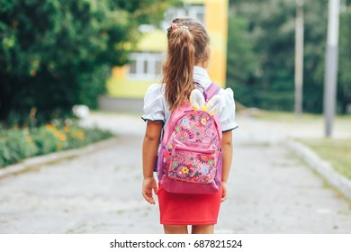 Schoolgirl with a backpack on her back. Back view