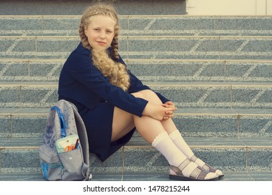 Schoolgirl with a backpack sitting on the steps in front of the school. Concept  school days, Back to school. girl in a  uniform with a backpack. pupil, learner, scholar