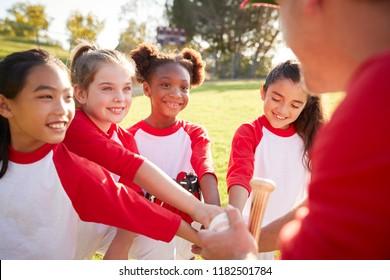 Schoolgirl baseball team in a team huddle with their coach