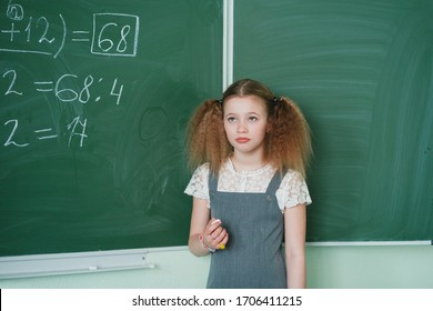 Schoolgirl at the blackboard ponders the answer.