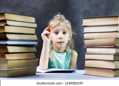 Schoolgirl, blonde girl with a stack of books and a pencil writes in a notebook. there is toning.