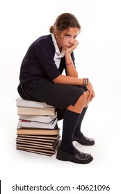 Schoolgirl with a bored look sitting on a pile of books