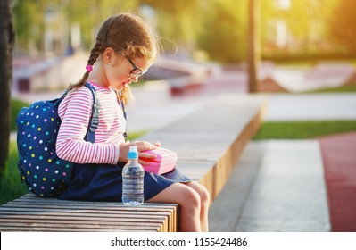 schoolgirl child eating lunch apples and bananas   at school