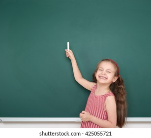 schoolgirl child in red striped dress point and drawing on green chalkboard background, summer school vacation concept