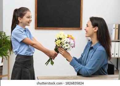 Schoolgirl congratulating her pedagogue with bouquet in classroom. Teacher's day