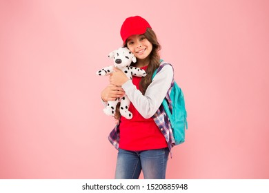 Schoolgirl daily life. Schoolgirl street style clothes. School club. Stylish schoolgirl. Girl little fashionable cutie with backpack carry soft toy dog. Take favorite toy with you. Reduce stress.
