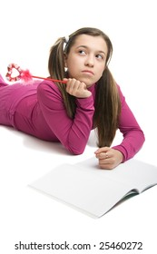 A schoolgirl doing her homework. Isolated on a  white background