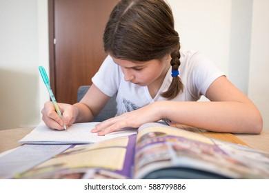 Schoolgirl is doing a homework