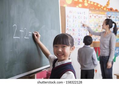 Schoolgirl doing math equation on the black board