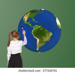 Schoolgirl drawning globe on the blackboard