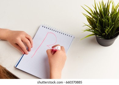 A schoolgirl draws a notepad on a notepad, a flower and a notepad on the table.