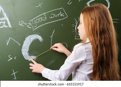 Schoolgirl draws on the blackboard