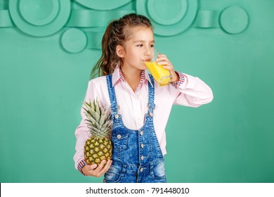 Schoolgirl is drinking pineapple juice for breakfast. The concept of a healthy lifestyle, food, childhood, vitamins, vegetarianism.