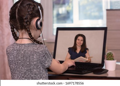 Schoolgirl during quarantine does homework via laptop, listening to the teacher on the monitor screen. Distance home schooling. Online education