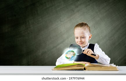 Schoolgirl examining opened book with magnifying glass. Elements of this image are furnished by NASA