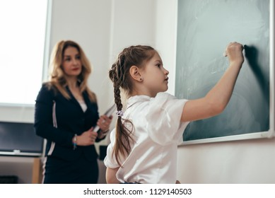Schoolgirl first-grader writing on chalkboard. School lesson Teacher and pupil.
