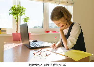 Schoolgirl, girl of 8 years, sitting at table with books and writing in notebook. School, education, knowledge and children