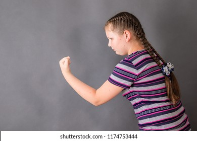 A schoolgirl girl full of determination threatens someone with her fist