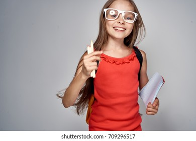 schoolgirl with glasses is happy on a gray background