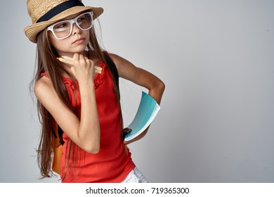 schoolgirl with glasses and hat thinks school notebooks on a gray background