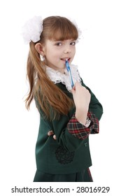 Schoolgirl is gnawing the pen. Portrait of smiling, little girl in school uniform.  Looking at camera. Isolated on white in studio.