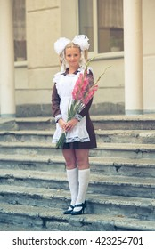 Schoolgirl graduate of the USSR with white bows and bouquet.The last bell and high school prom.