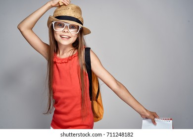 schoolgirl happy with glasses holding a hat on her shoulders backpack in the hands of a school notebook on a gray background