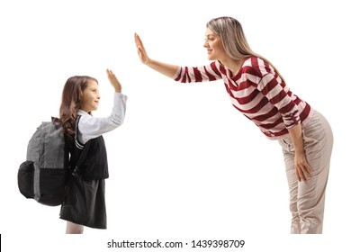 Schoolgirl high-fiving with a young woman isolated on white background