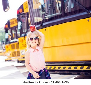 Schoolgirl holding the apple on head and smiling. Back to school idea.