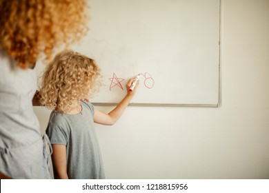 Schoolgirl in home wear writing something on white board on the wall with a marker and her mother looking at her. Learning and school concept.
