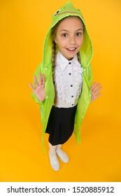Schoolgirl hooded raincoat going to school. Waterproof fabric for your comfort. Rainproof accessory. Waterproof clothes. Kid girl happy wear raincoat. Rain is not hindrance. Waterproof cloak.