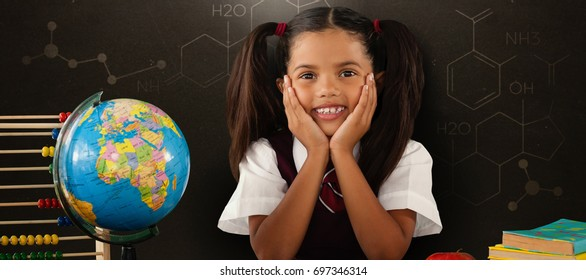 Schoolgirl leaning by globe and books against blackboard
