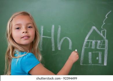 Schoolgirl learning the alphabet on a blackboard