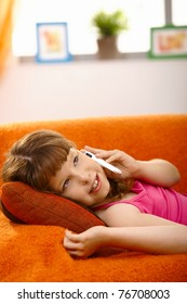 Schoolgirl lying on couch talking on mobile phone, smiling,?