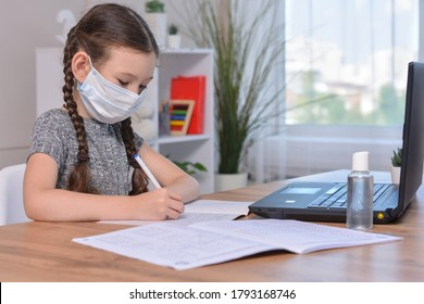 A schoolgirl in a medical mask is doing her homework on a laptop at home or studying in class at a lesson at school.Student safety after covid-19 pandemic. Back to school.Distance learning.